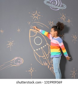 African-American child playing with chalk rocket drawing on grey background