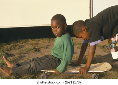 African-American children playing with a skateboard, Los Angeles, CA
