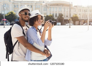 African-american couple exploring new city, taking photos on camera, copy space