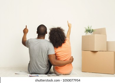 African-american family couple looking up, sitting on floor in new apartment with moving boxes, dreaming about future, point upward, back view, copy space, isolated