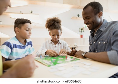 african-american family playing board game in cafe