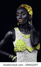 African-american fashion style. Beautiful African woman looking at camera with bright creative yellow makeup wearing headscarf and bathing suit handmade.