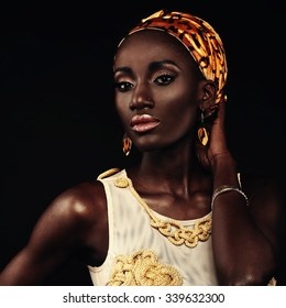 African-american fashion style. Beautiful African woman wearing headscarf and gold bathing suit handmade looking at camera while standing against black background.