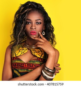 African-american fashion style. Beautiful African woman wearing color dress and bijou looking at camera while standing against yellow background. Latin woman with makeup, nail polish and hairstyle.