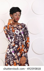 African-american fashion style. Beautiful African woman wearing color dress looking down. Latin woman with makeup and hairstyle. Young beautiful African fashion model with traditional dress.