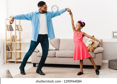 African-american father dancing with little daughter at home