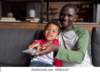 african-american father and son with remote control watching tv