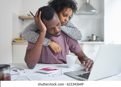 African-american female hugging her unemployed husband, while he looking at laptop, using online banking with frustrated expression, not able to pay off utility bills. Financial problems concept