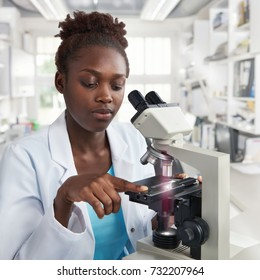 African-american female scientist, student or tech in lab coat works in modern laboratory with a microscope