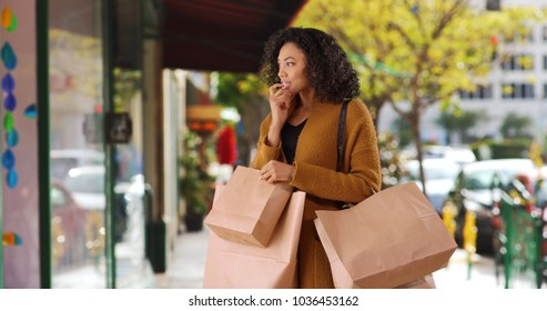 African-American female shopaholic checking out window display of city shop