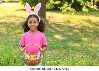 African-American girl with basket of Easter eggs in park