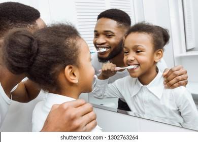 African-american girl brushing teeth with dad in bathroom
