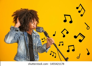 African-American girl with microphone singing against color background