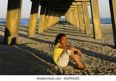 African-american girl sitting on the sand at the beach with a pier in the background.