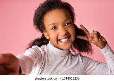 African-american girl taking selfie and having fun over pink background