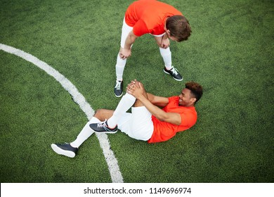 African-american guy in football uniform lying on field with his knee in pain while other player leaning over him