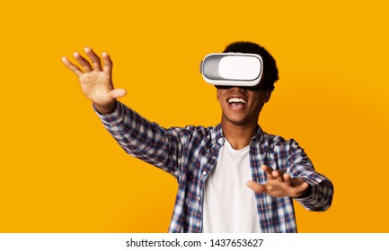 African-American Guy Using VR Headset and Experiencing Virtual Reality, Yellow Background