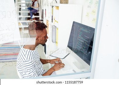 African-american it-specialist looking attentively at coded data on computer screen while working in office
