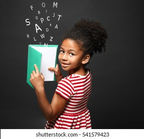 African-American little girl with book and alphabet letters on dark background. Speech therapy concept