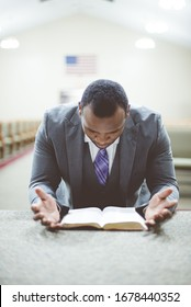 An African-American male praying with his head down looking at the Bible at the church