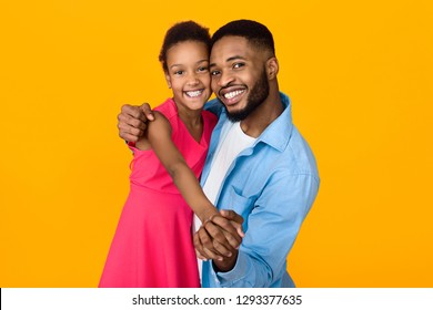 African-american man dancing with daughter over yellow background