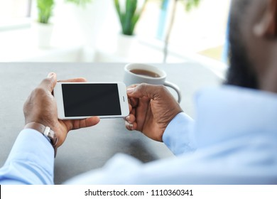 African-American man holding mobile phone with blank screen in hands at table indoors