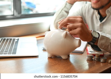 African-American man putting coins into piggy bank on table. Savings concept