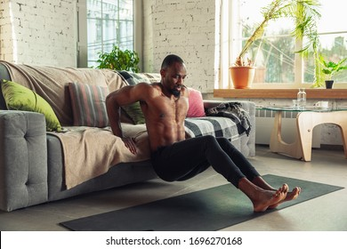 African-american man teaching at home online courses of fitness, aerobic, sporty lifestyle while being quarantine. Getting active while isolated, wellness, movement concept. Training upper body.