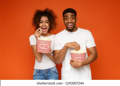 African-american man and woman eating popcorn, watching movie on orange background