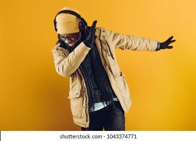 African-American man in yellow hat, jacket and headphones listening to music and dancing