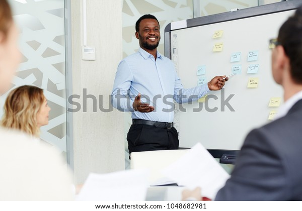 African-american manager standing by whiteboard and presenting his ideas for new project for company