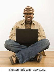 African-American mid-adult man sitting on floor smiling at viewer on laptop computer.