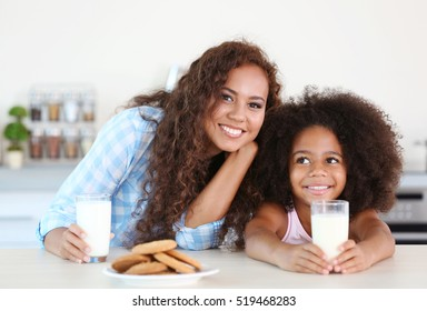 African-American mother and daughter having breakfast with milk in the kitchen