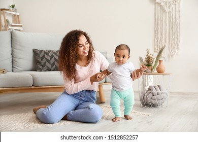 African-American mother teaching her little baby to walk at home