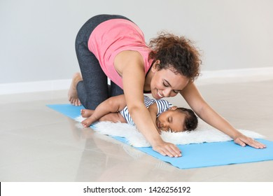African-American mother training with cute little baby at home