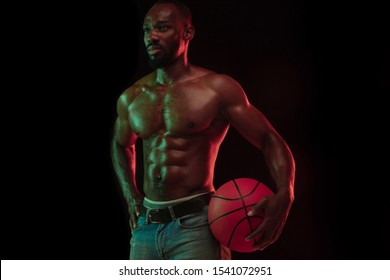 African-american muscular young basketball player in action of gameplay training, practicing in neon lights over dark studio background. Concept of sport, movement, energy, dynamic, healthy lifestyle.