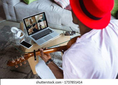 African-american musician playing guitar during online concert at home isolated and quarantined. Using camera, laptop, streaming, recording courses. Concept of art, support, music, hobby, education.