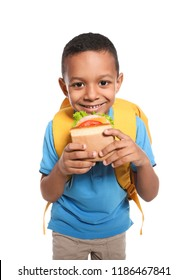 African-American schoolboy with healthy food and backpack on white background
