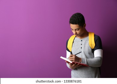 African-American schoolboy writing in notebook on color background