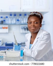African-american scientist or graduate student in lab coat and protective gloves smiles at the camera