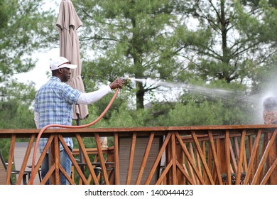 African-American spraying  a  deck with a water hoses