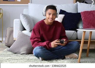 African-American teenage boy playing video games at home