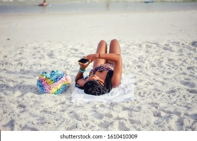 African-American teenage girl on the beach in Florida for spring break vacation and texting on her cell phone-teen