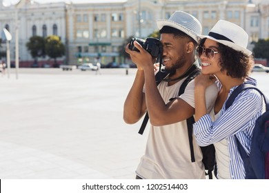 African-american tourist couple taking photos of city architecture on camera, copy space