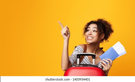 African-American Tourist Pointing Finger Away And Holding Tickets Over Orange Background, Copy Space