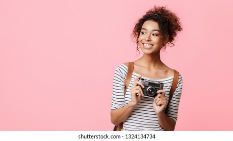 African-american traveller with retro camera looking away at copy space, pink background