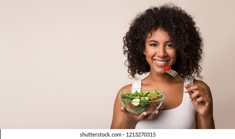 African-american woman eating vegetable salad over light background with copy space - Shutterstock ID 1213270315