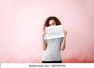 African-American woman holding calendar with marked days of menstruation on color background