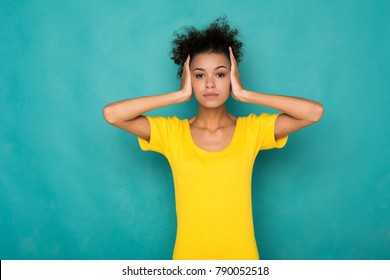 African-american woman puts her hands on head. Portrait of young serious girl closing her ears, hear nothing, deafness concept