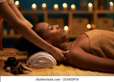 African-American woman receiving relaxing massage in spa salon